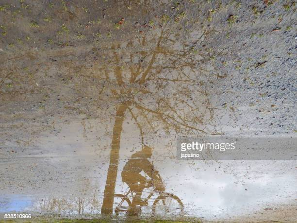 cyclist reflected in a puddle - sacrifice play stock pictures, royalty-free photos & images