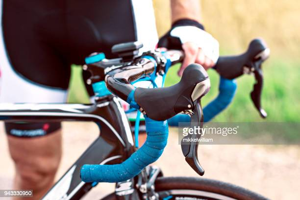 Cyclist relaxes and holds on to handlebar of professional racing bike
