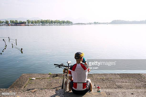 Cyclist relaxing on the lakeshore of the West lake