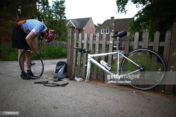 A cyclist repairs a puncture during the London to Brighton Bike Ride on June 16 2013 in Smallfield England Every year since 1980 cyclists gather to...