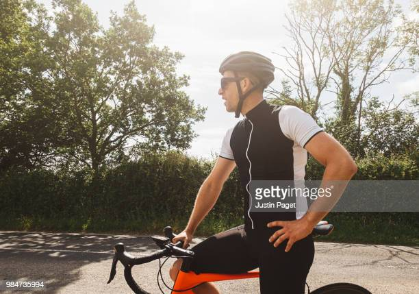 cyclist resting by road side - mid adult men stock pictures, royalty-free photos & images
