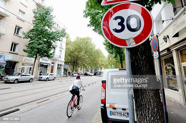 A cyclist ride through the city on September 15 2015 in Grenoble southeastern France Grenoble district council will limit car velocity to 30km per...