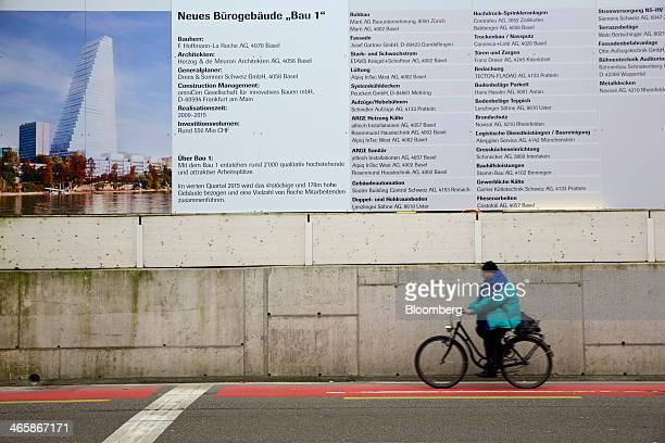 A cyclist rides a bicycle past an information board surrounding a construction site at Roche Holding AG's headquarters in Basel Switzerland on...