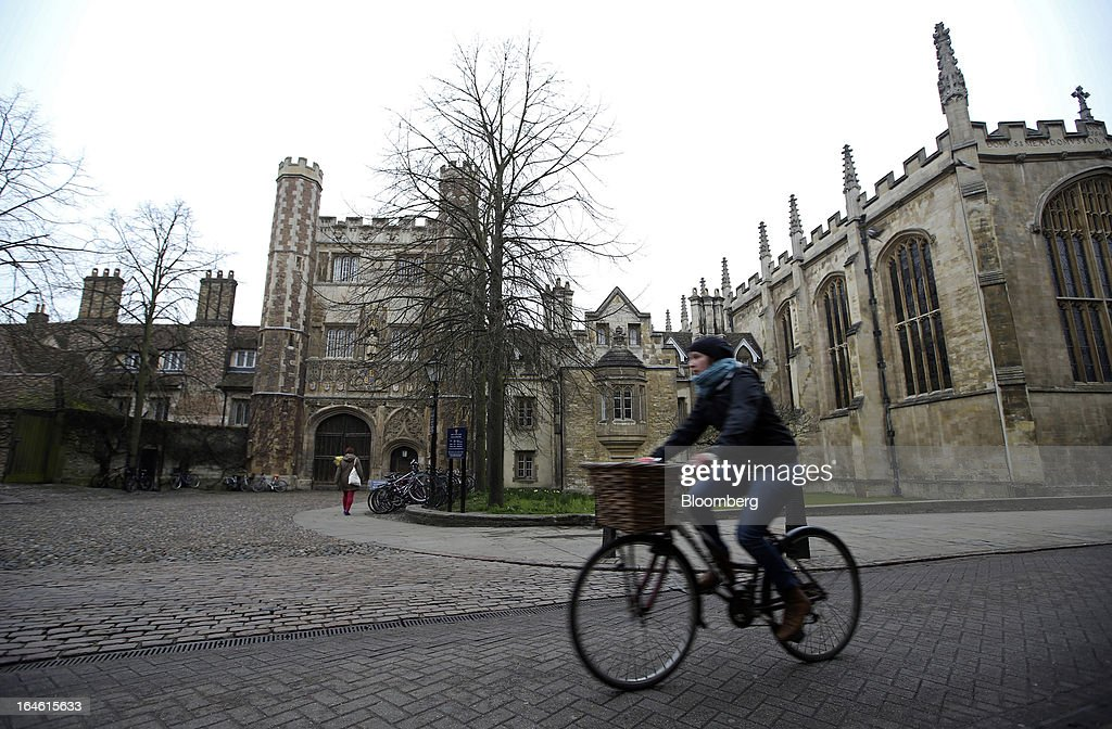 A cyclist rides a bicycle past Trinity College, part of the University of Cambridge, in Cambridge, U.K., on Friday, March 22, 2013. In 2011, the U.K.'s government unveiled a plan to reduce state spending on higher education and shift more of the costs to students through tuition increases and a loan program. Photographer: Chris Ratcliffe/Bloomberg via Getty Images