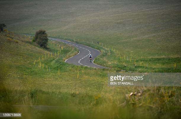 A cyclist rides a bike along an empty road near Beachy Head close to Eastbourne on the south coast of England on April 12 as life in Britain...