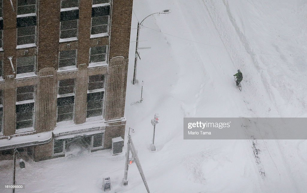A cyclist rides a bike through the snow in the Back Bay neighborhood during a lingering blizzard on February 9, 2013 in Boston, Massachusetts. The powerful storm has knocked out power to 650,000 and dumped more than two feet of snow in parts of New England.