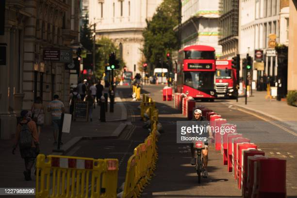 A cyclist rides a hire bicycle beside roadside barriers on a temporary bike lane in The City of London in London UK on Monday Aug 10 2020 With a...