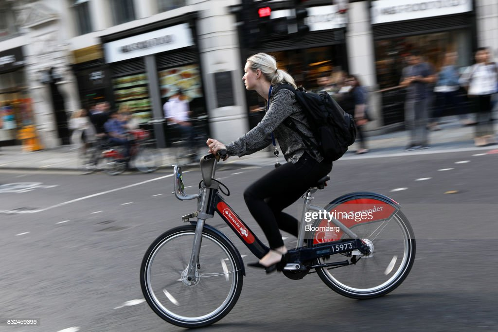 A cyclist rides a hired bicycle displaying logos of sponsor Banco Santander SA in London, U.K., on Tuesday, Aug. 15, 2017. Banco Santander, Spains biggest lender, has bought minority stakes in three financial-technology firms as ChairmanAna Botinmakes machine learning a hallmark of her growth plan. Photographer: Luke MacGregor/Bloomberg via Getty Images