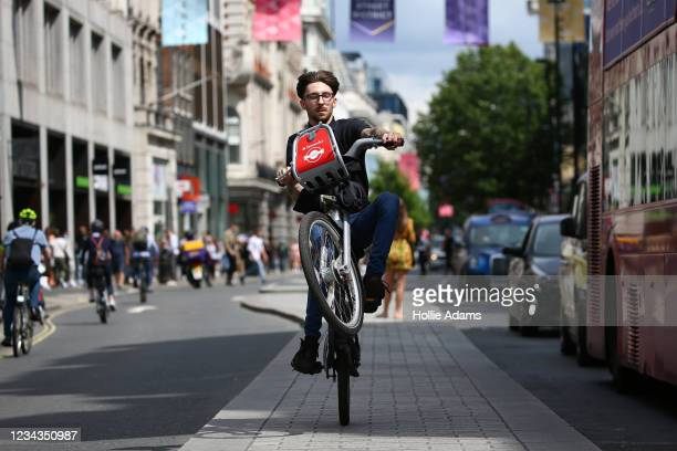 Cyclist rides a Santander Bicycle in the middle of the road on Oxford Street on July 31, 2021 in London, England. The United Kingdom, considered one...