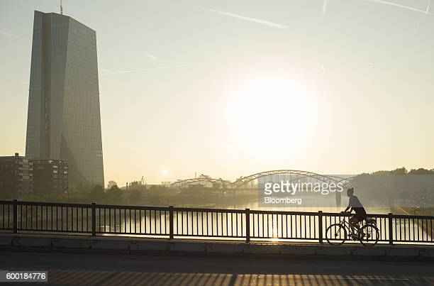 A cyclist rides across a bridge as the skyscraper headquarters of the European Central Bank stands beside the River Main in Frankfurt Germany on...