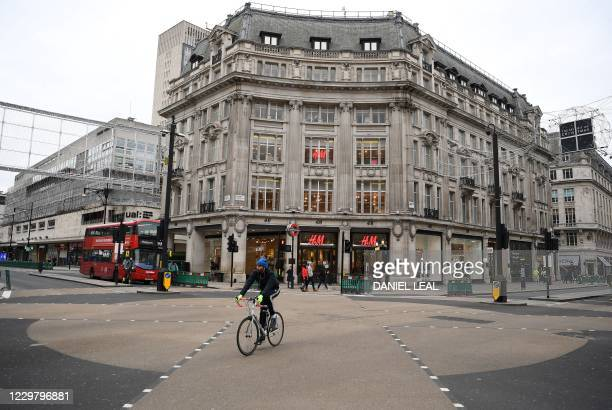 Cyclist rides across an almost deserted Oxford Circus on Oxford Street in London on November 26, 2020. - Britain's government on Wednesday unveiled...