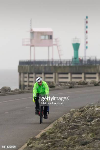 A cyclist rides across Cardiff Bay barrage as Hurricane Ophelia approaches the west coast of the United Kingdom on October 16 2017 in Cardiff Wales...