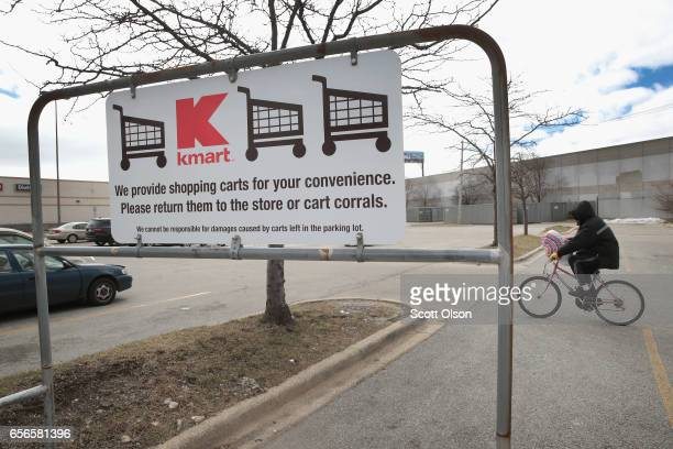 A cyclist rides across the parking lot of a Kmart store on March 22 2017 in Chicago Illinois Sears Holdings the parent of Kmart and Sears Roebuck Co...