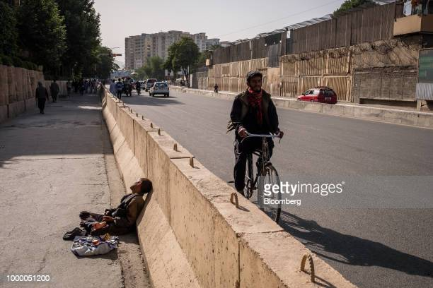 A cyclist rides along a road past a shoe shiner waiting for customers in Kabul Afghanistan on Thursday July 12 2018 US President Donald last year...