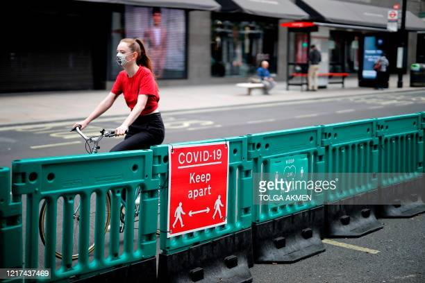 Cyclist rides along on Oxford Street, where barriers have been installed to widen he pavement to enable social distancing due to the COVID-19...