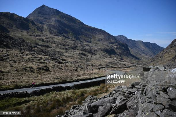 Cyclist rides along the near-deserted A4086 at Pen-y-Pass, near to Mount Snowdon, in north Wales on April 5, 2020 as the warm weather tests the...