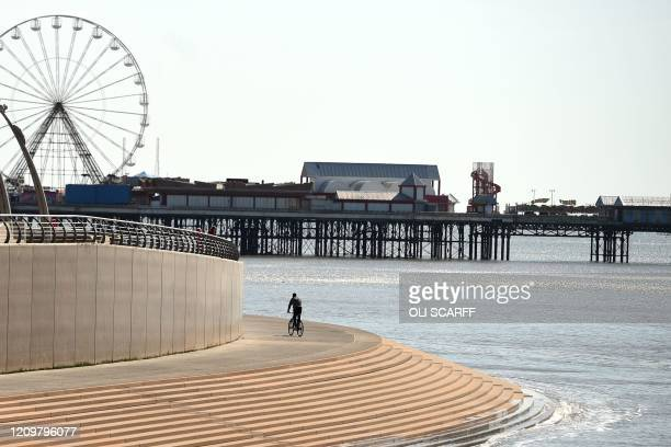 Cyclist rides along the promenade toward the central pier in the spring sunshine on the coast in Blackpool, north-west England on April 13 during the...