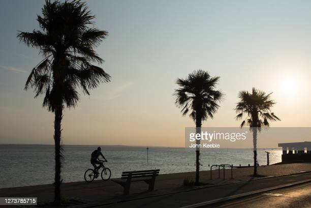 A cyclist rides along the sea front as the sun goes down during the recent warm weather on September 20 2020 in Southend on Sea London