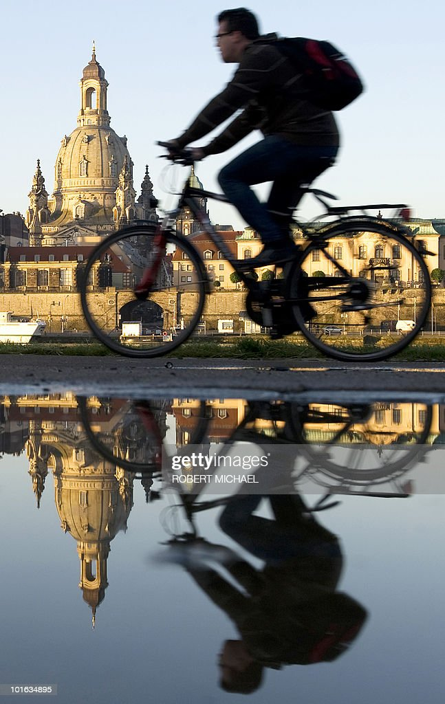 A cyclist rides along the the banks of the river 'Elbe' with the Church of Our Lady (Frauenkirche) in Dresden, eastern Germany, on June 4, 2010, as the sun shines after long weeks of bad weather