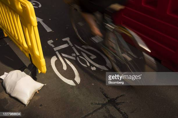 A cyclist rides alongside a bus on a temporary bike lane in London UK on Monday Aug 10 2020 With a budget of £2 billion over the next five years...
