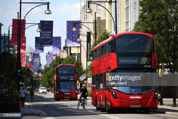 Cyclist rides around a London bus on Oxford Street on July 18, 2021 in London, England. On Monday, England will drop nearly all remaining...