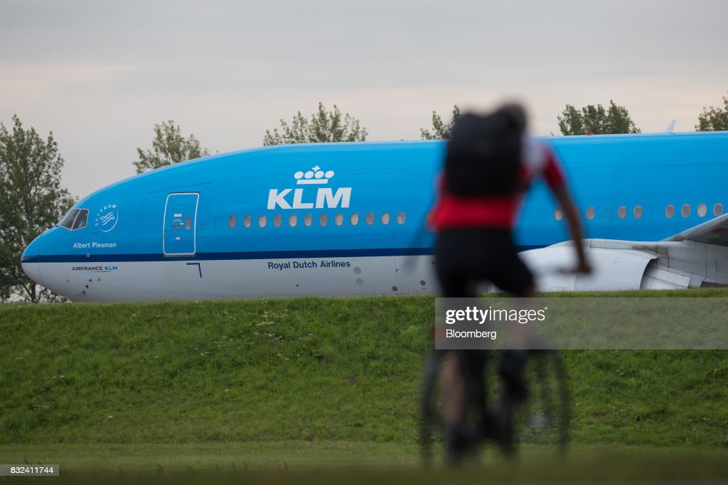A cyclist rides as a KLM passenger plane, operated by the Dutch arm of Air France-KLM Group, stands at Schiphol airport in Amsterdam, Netherlands, on Tuesday, Aug. 15, 2017. Delta Air Lines Inc., China Eastern Airlines Corp. and Air France-KLM Group are reaching for their checkbooks to forge a deeper global alliance. Photographer: Jasper Juinen/Bloomberg via Getty Images