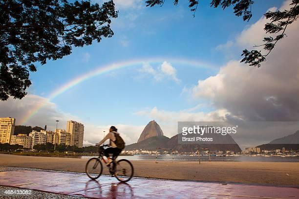 Cyclist rides at Botafogo beach enjoying the view of Sugar Loaf under the rainbow Rio de Janeiro lifestyle Brazil