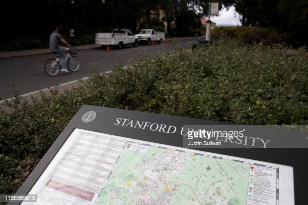 Cyclist rides by a map of the Stanford University campus on March 12, 2019 in Stanford, California. More than 40 people, including actresses Lori...