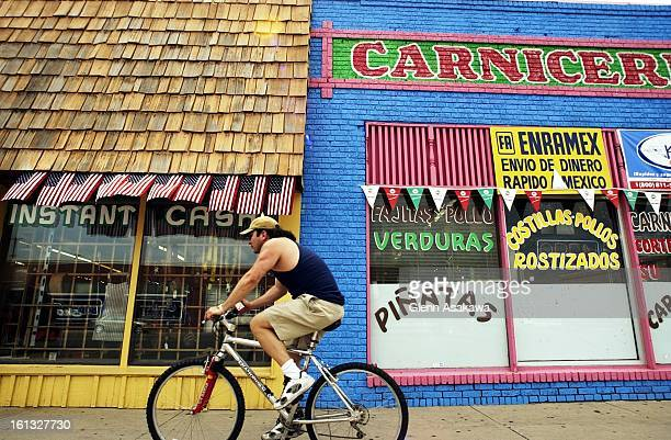 A cyclist rides by a pawn shop sporting American flags located next to a Mexican corner market near 11th St and 8th Ave in Greeley Controversial...