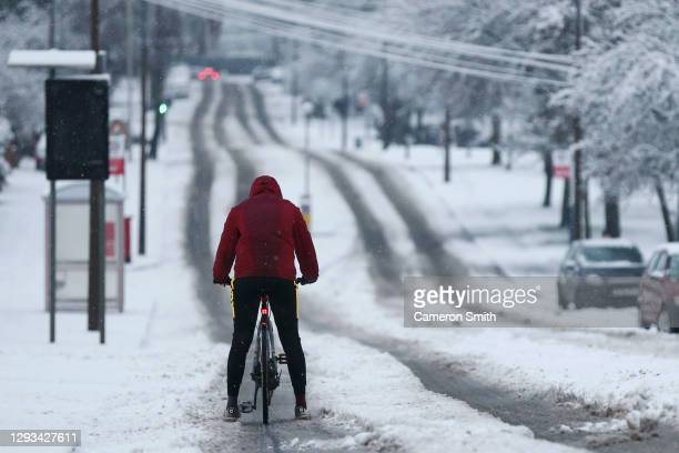 Cyclist rides down a snow covered road as heavy snowfall falls down on the West Midlands overnight on December 28, 2020 in Stourbridge, England....