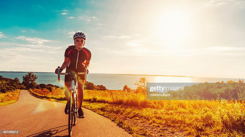 Cyclist rides her bike up a steep hill at sunset : Stock Photo