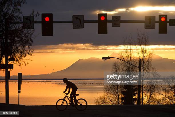 A cyclist rides his bike as a lateday sun peeks through the clouds over Cook Inlet in downtown Anchorage Alaska on Tuesday April 2 2013