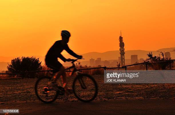 A cyclist rides his bike backgrounded by the city skyline during the sunset over Pretoria on June 30 2010 AFP PHOTO/JOE KLAMAR