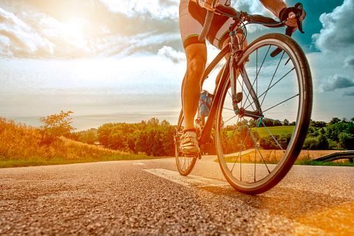 Cyclist rides his bike up a steep hill 498375904