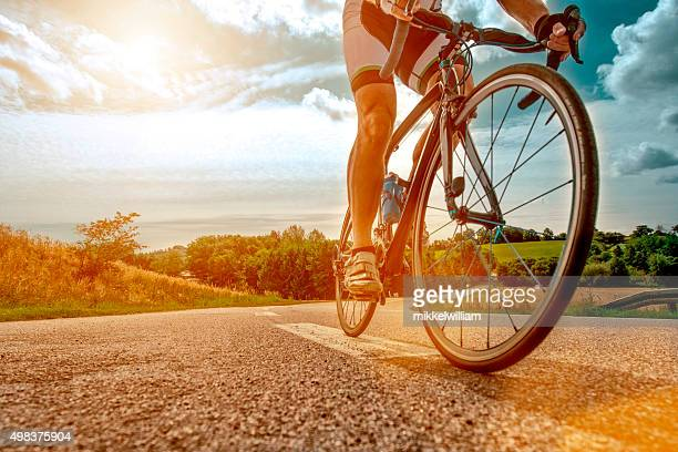 cyclist rides his bike up a steep hill - riding stock pictures, royalty-free photos & images