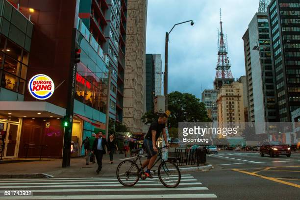 Cyclist rides in front of a Burger King do Brasil restaurant on Paulista Avenue in Sao Paulo, Brazil, on Monday, Dec. 11, 2017. Burger King do Brasil...