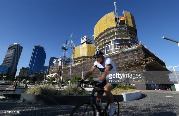A cyclist rides in front of a construction site in the Elizabeth Quay area of Perth Australia on Wednesday April 11 2018 Australia is scheduled to...