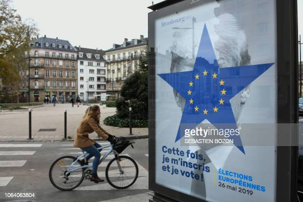 A cyclist rides near a street poster depicting the twelvestar circle from the European Union flag within a blue fivepointed star covering the face of...