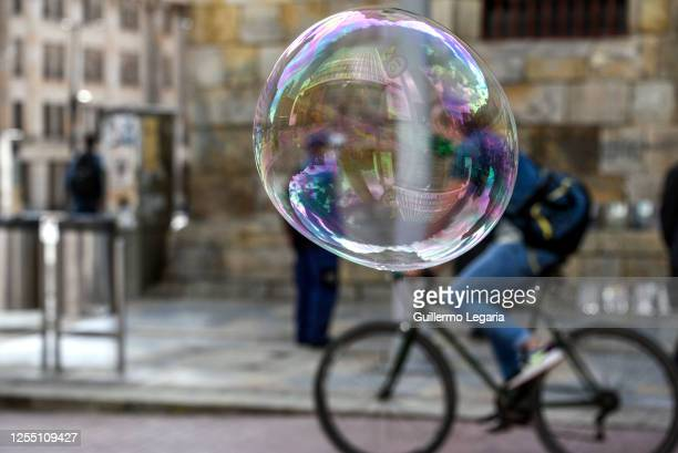 Cyclist rides next to a soap bubble on a pedestrian street on July 08, 2020 in Bogota, Colombia. After 15 consecutive weeks of preventive mandatory...