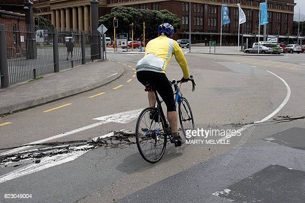 A cyclist rides over a damage road on the Wellington water front after a 78 earthquake centred in the South Island in Wellington on November 14 2016...