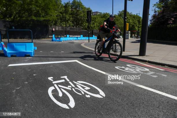 Cyclist rides over road markings in a new bicycle lane created by Transport for London on Park Lane in London, U.K., on Thursday, May 28, 2020. To...