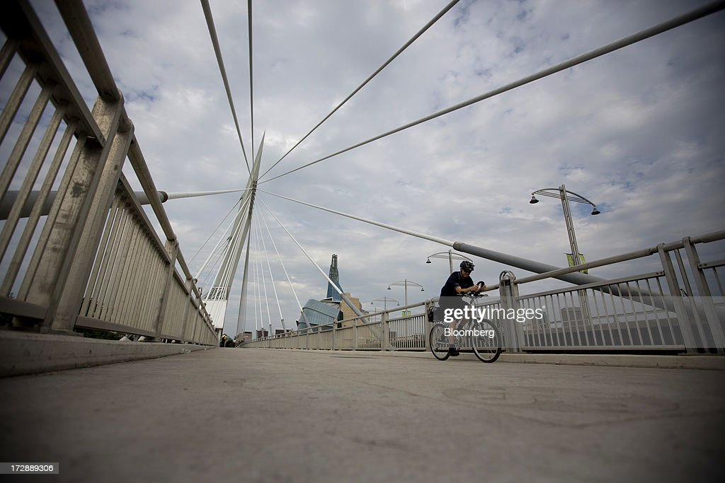 A cyclist rides over the Provencher Bridge in Winnipeg, Manitoba, Canada, on Thursday, July 4, 2013. Canada extended the longest streak of merchandise trade deficits in a quarter century in May, with the shortfall narrowing as imports fell faster than exports. Photographer: Brent Lewin/Bloomberg via Getty Images