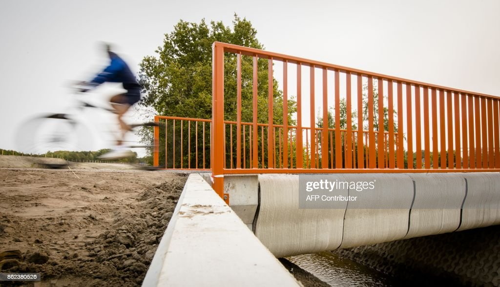 A Cyclist rides over what has been named as the world's first 3-D printed concrete bridge after its opening in Gemert, The Netherlands on October 17, 2017. Dutch officials toasted the opening of what is being dubbed as the world's first 3D-printed concrete bridge, which is primarily meant to be used by cyclists.There was applause as officials wearing hard hats and workmen's jackets rode over the bridge on their bikes at the inauguration in the southeastern town of Gemert. PHOTO / Bart Maat