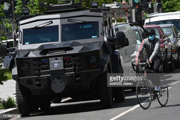 A cyclist rides pass an armoured vehicle heading towards Lafayette Square on 16th Street as people protest the death of George Floyd an unarmed black...