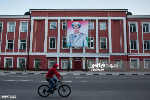 A cyclist rides past a banner featuring an image of Tajikistan President Emomali Rahmon displayed on a building in Dushanbe Tajikistan on Sunday...