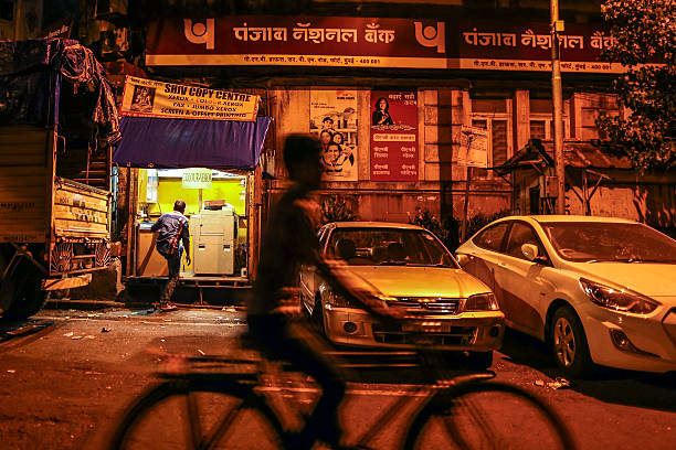 A cyclist rides past a branch of Punjab National Bank in Mumbai India on Saturday Oct 19 2013 Volatility in Indias rupee fell to a twomonth low on...