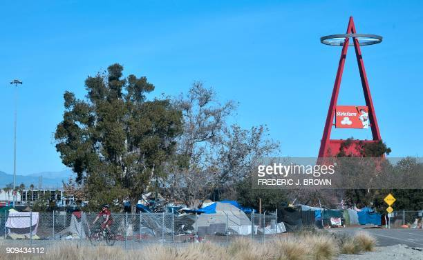 A cyclist rides past a homeless encampment near Angel Stadium in Anaheim California on January 23 2018 January 22 reports said authorities planned to...