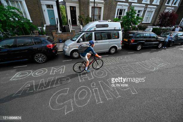 A cyclist rides past a message chalked onto the road outside the home of Number 10 Downing Street special advisor Dominic Cummings in London on May...