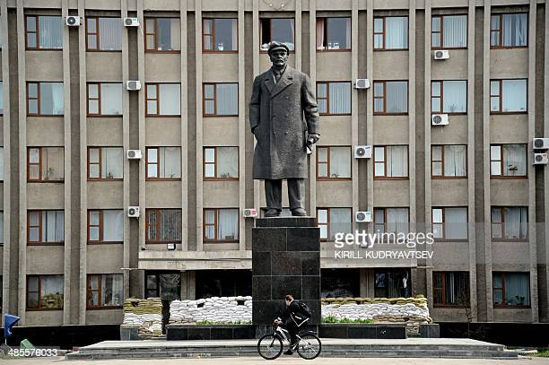 A cyclist rides past a monument of late Soviet leader Vladimir Ilyich Lenin close to the regional administration building in the eastern Ukrainian...