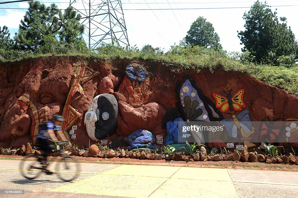 A cyclist rides past a piece by Colombian artist Carlos Andres Gomez during World Environment Day in Cali, Valle del Cauca departament, Colombia on June 5, 2010. Gomez sculpts figures on the mountain to raise awareness of the importance of the environment. AFP PHOTO/Luis ROBAYO